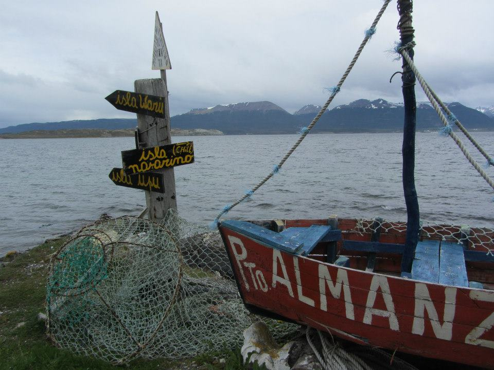 A boat, a signpost and Chile across the water.